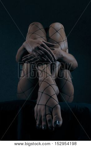 Low key special toned photo of long beautiful sexy female legs in net stockings and hands holding legs against dark background