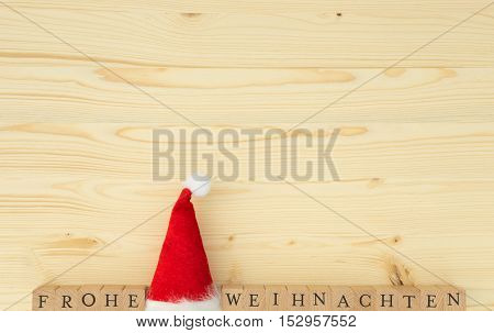 Christmas hat and the german words for Merry Christmas (Frohe Weihnachten) on wood, spruce, fir
