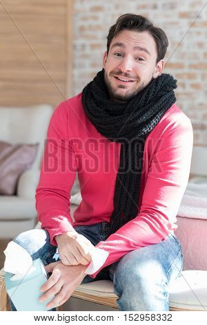 Need to stay in warmth. Pleasant optimistic young man sitting on the bed and wearing a scarf while being ill