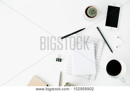 Flat lay top view office table desk. Workspace with blank diary headphones coffee succulent and watch on white background.