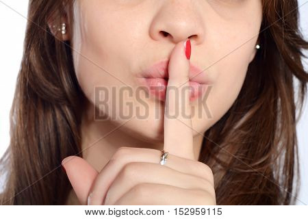 Potrait of a young beautiful woman making silence gesture. Isolated white background.