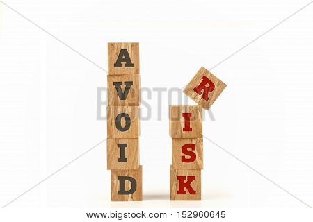 Avoid Risk word written on cube shape wooden surface isolated on white background.