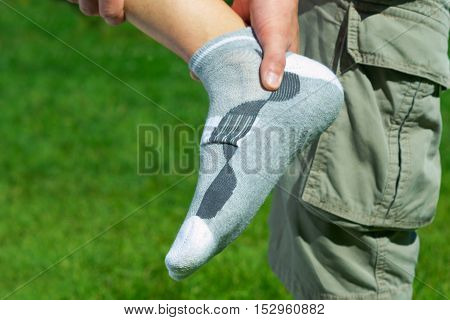 pain in the foot feet on the background of green grass