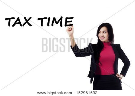 Beautiful businesswoman makes a text of tax time on whiteboard to reminder the tax return
