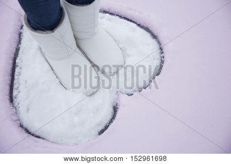 Heart on snow. The girl loves winter