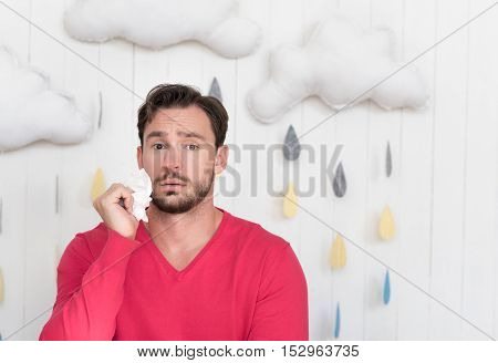 Being depressed. Sad ill young man standing isolated against cloudy background and holding a paper tissue while suffering from an illness
