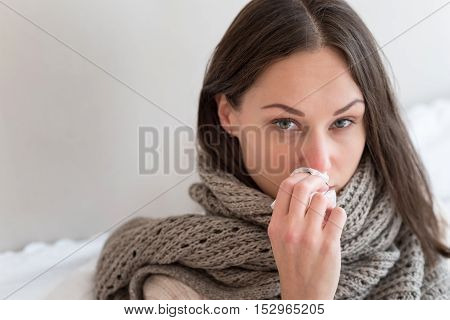 Flu symptoms. Depressed cheerless young woman holding a paper tissue and wiping her nose while suffering from flu