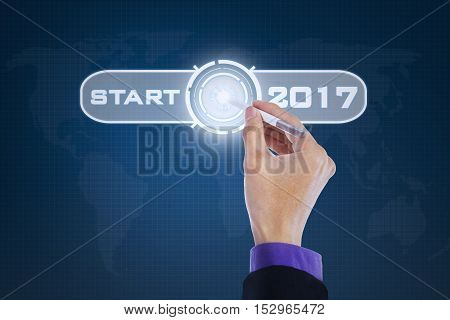 Image of businessman hand pressing start button by using a stylus pen with numbers 2017 on the virtual screen