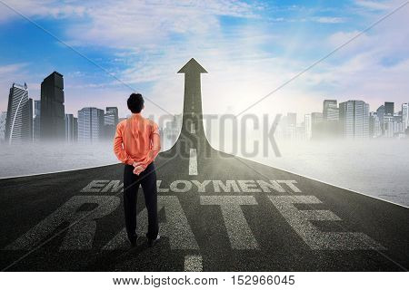 Male worker standing on the road with employment rate text and looking at upward arrow