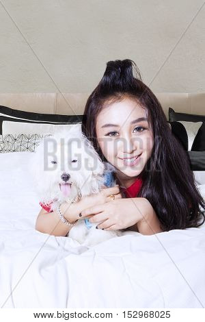 Happy young woman and maltese dog playing in bedroom while looking at the camera