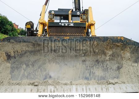 Tyumen, Russia - September 15, 2007: Construction of pedestrian quay on Tura river. Digger, heavy duty construction equipment parked at work site