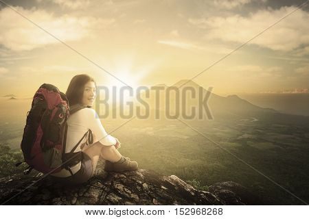 Rear view of young woman hiker sitting on a mountain peak while smiling and looking at the camera