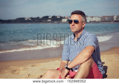 Handsome man. Outdoor male portrait. Middle-aged man resting at seafront in sunglasses, summer outdoor portrait, image toned.
