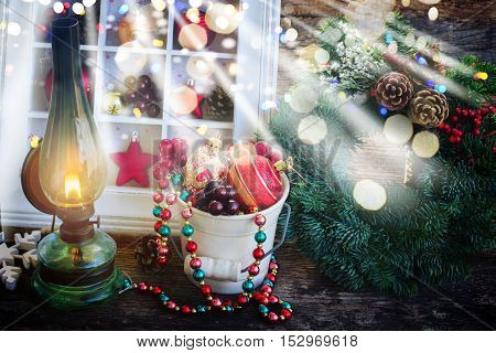 vintage glowing lantern with evergreen christmas wreath and decorations, low key with glimming lights