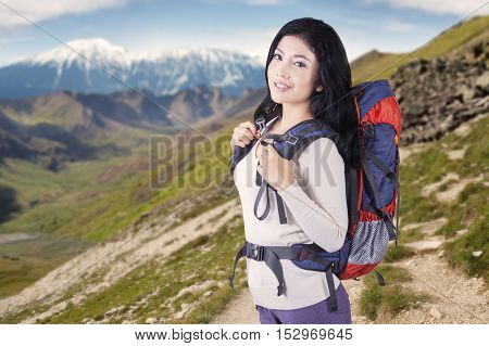 Image of beautiful young female ascending a mountain with a backpack in sunny day