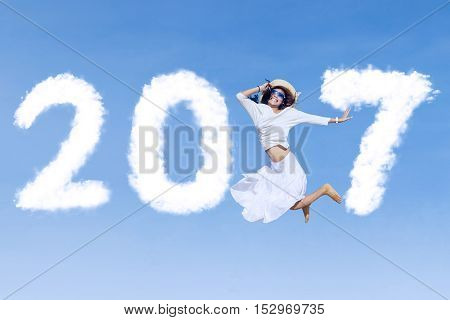 Concept of New Year 2017. Beautiful young woman jumping on the blue sky with cloud shaped number 2017