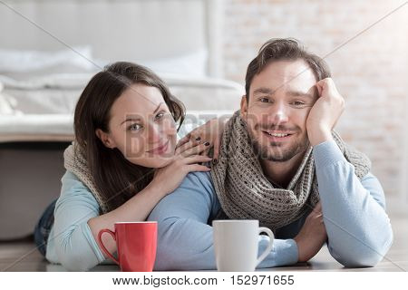 Positive emotions. Cheerful happy young couple looking at you and smiling while being in a great mood