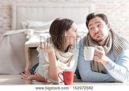Involved in the conversation. Cheerful good looking nice couple looking at each other and having tea while having a conversation.