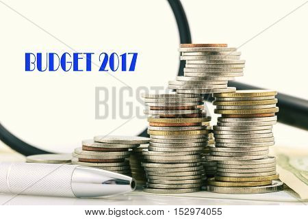 pile of coins and pen and magnifying glass with word Budget 2017 on banknotes white backgroundconcept finance and banking