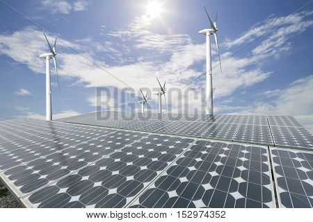 Solar panels and wind turbine with blue sky background