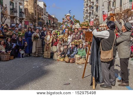Putignano,Apulia,Italy - February 15, 2015: carnival masks representing Italian peasant population of the past; it is a scene of a group photo of a farmer wedding.In the background float of Merkel.