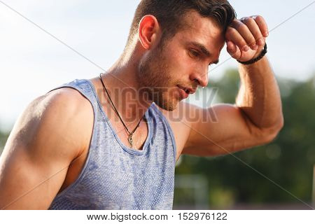 Tired wet athletic man in sports blue t-shirt wiping sweat his hand on nature background