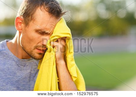 Athletic man wipes his face with yellow towel after training outdoor