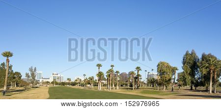 A green lawn stretching from Encanto park to downtown of Phoenix Arizona; Copy space in clear blue sky