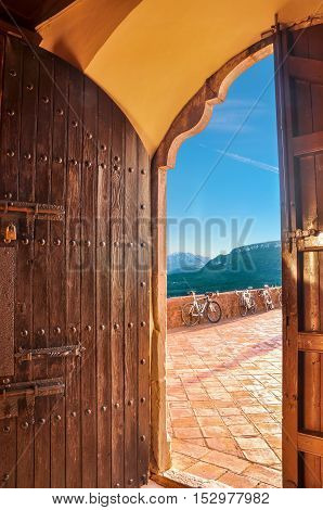 Beautiful view from the open door of antique church on mountain scene with last beams of setting sun and sports bicycles parked on observation platform. Healthy lifestyle concept. Vertical.