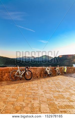Beautiful mountain scene in last rays of setting sun and four sport bikes parked on the observation platform. Healthy lifestyle concept. Vertical.