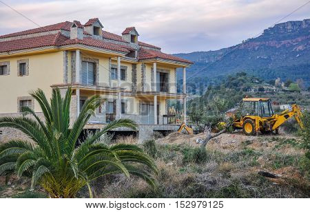 Construction site with unfinished new house and yellow excavator on the background of beautiful mountain scene. Horizontal.