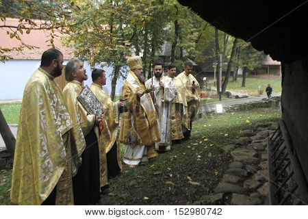 BUCHAREST ROMANIA - OCTOBER 23 2016: Episcopal vicar Timotei Prahoveanul performs church sanctification of a 18th century wooden church in National Village Museum.
