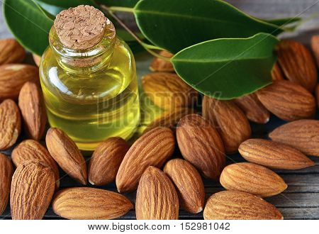 Almonds seed and almond oil on old wooden background for beauty spa and treatment.Selective focus.