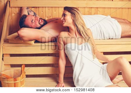 Picture of happy couple relaxing in wooden sauna
