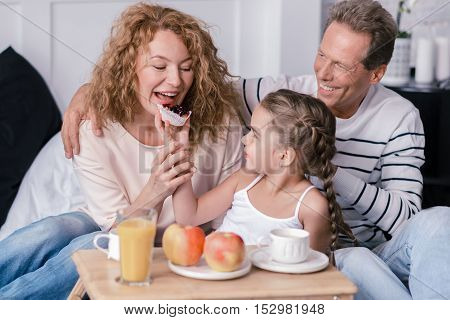 We eating bakery. Smiling little girl sitting at the breakfast tray on the bed while eating cupcakes with her grandparents at home