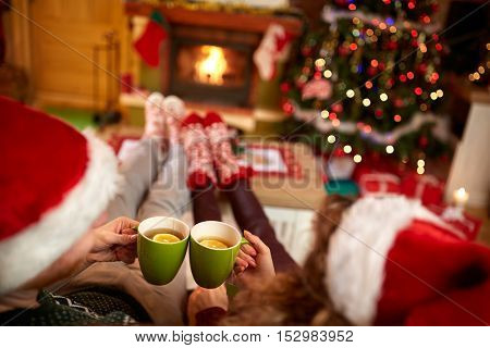 Couple toasting with tea coups for Christmas holiday