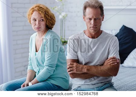 I beg you to forgive. Upset husband and wife sitting back to back on the bed with crossed arms while having a quarrel