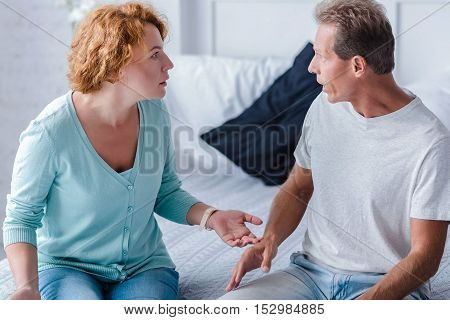 How can you do to me like this. Shocked couple sitting on the bed while arguing