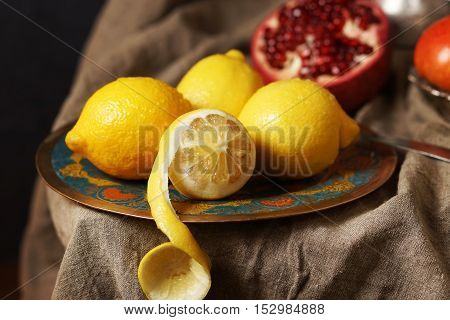 Beautiful lemons on a plate, one cut skin. In the background of grenades.