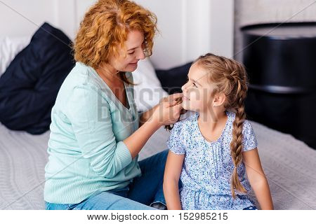 Making hairstyle. Cheerful smiling grandmother plaiting braids to her little granddaughter while having fun at home
