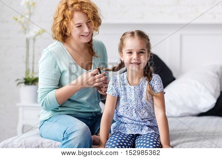 Happiness and peacefulness. Smiling grandmother plaiting braids to her little granddaughter while having fun at home
