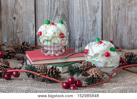 horizontal image of two bowls of ice cream with green and red bubblegum balls on top  sitting on two books with pine cones and decorative cranberries on burlap with an old wood plank background