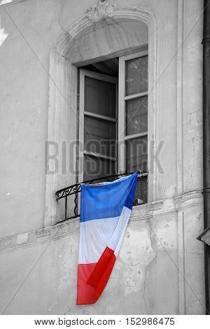 French Flag Hanging on the Window of a Building to Pay Homage to the Victims of Terrorist Attacks in France