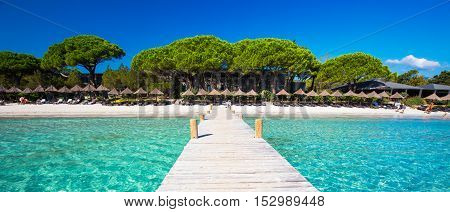 CORSICA FRANCE - August 29 2016 - Bidge leading to beach resort in Santa Giuliana beach with pine trees and azure clear water Corsica France Europe.