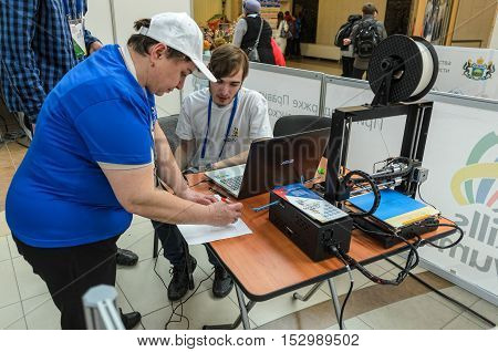 Tyumen, Russia - March 24. 2016: Open championship of professional skill among youth. World skills Russia Tyumen - 2016. The participant of a competition receives task for printing on 3D printer