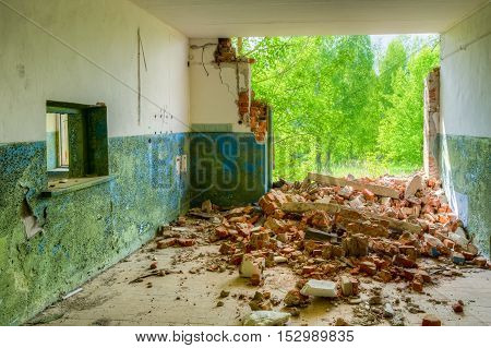 Destroyed Abandoned Rural Shop With Ruined Brick Wall In Nuclear Contamination Zone After Chernobyl Catastrophe. Exclusion Area With Opulent Vegetation In Summer Spring Sunny Day