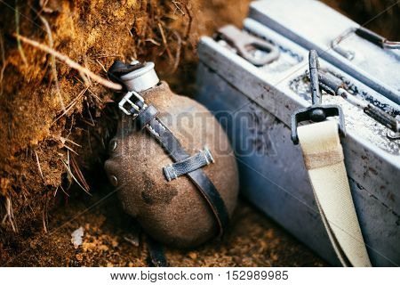 German military ammunition of World War II on ground. Flask, box of ammunition.