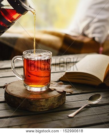 Herbal tea in glass cup in cozy ambience.