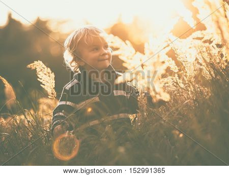 Happy Little Boy Playing Outdoor In Beautiful Autumn Scenery