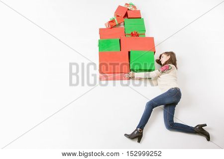Black Friday 2016 at United States Funny mother holding many gift boxes for kids and running. Copy space at white background. Big gift box Cristmas shopping. Xmas, New Year holiday Merry Christmas